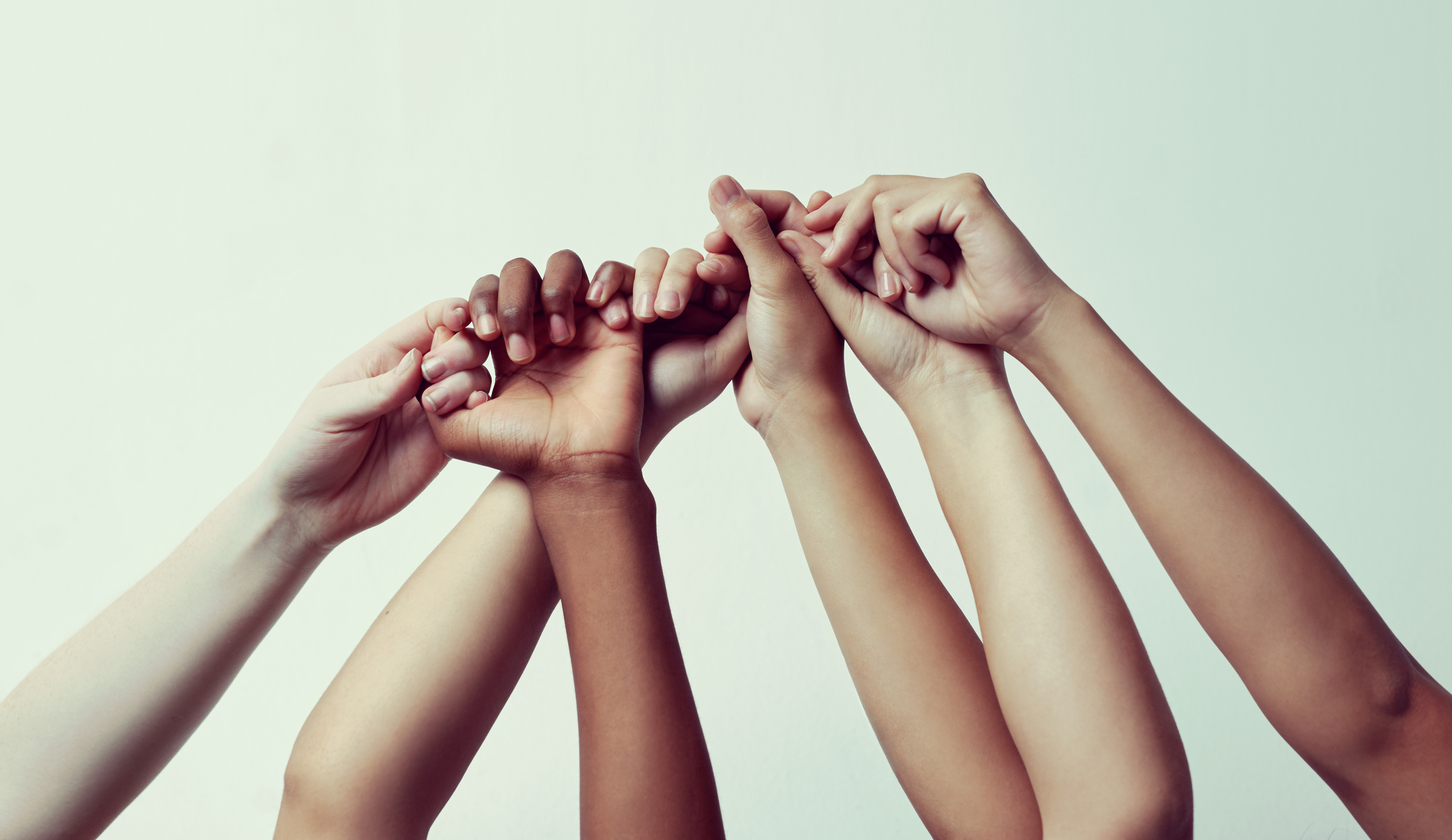 Image of women of different ethnicities holding their raised hands together